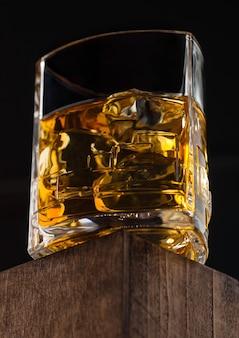 Luxe kristalglas met ijsblokjes scotch whisky bovenop houten kist en zwarte achtergrond