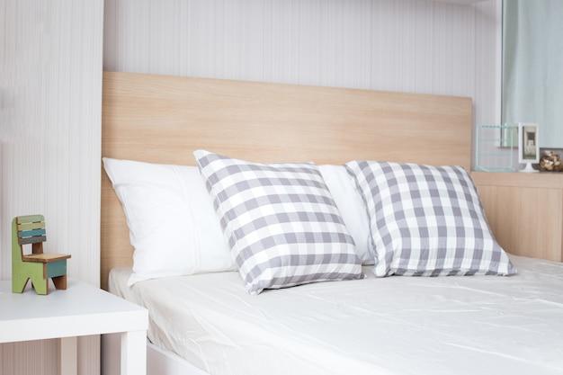 Luxe kussens op wit bed in de slaapkamer