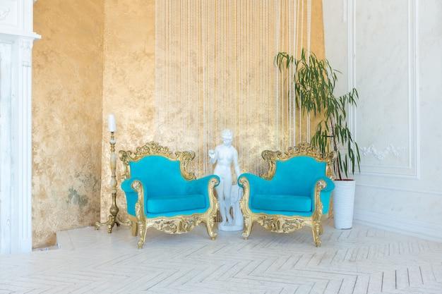 Luxe licht interieur van woonkamer met gouden muur en chique dure meubels in witte en gouden kleuren