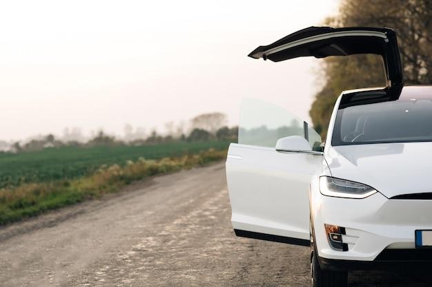Luxe modern voertuig langs bomen en velden