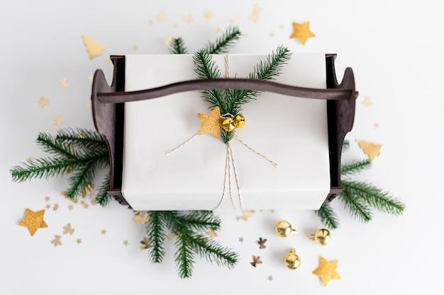 Luxe nieuwjaarsgeschenk met gouden decoratie en boomtakken. kerstcadeau in houten mandje. kerstmisachtergrond met giftdoos. presenteert voor kerstviering.