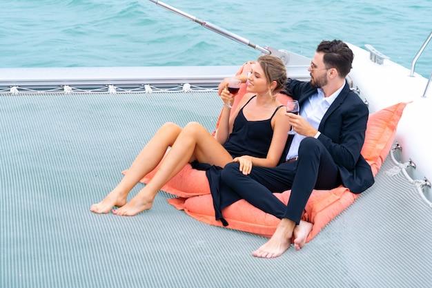 Luxe ontspannende paarreiziger in mooie jurk en suite zit op een zitzak en drinkt een glas wijn in een deel van het cruisejacht.