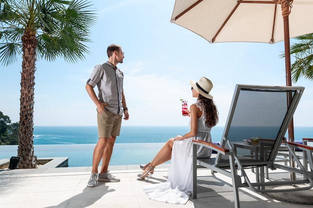Luxe paar rusten in de buurt van het zwembad en kijken naar de horizon