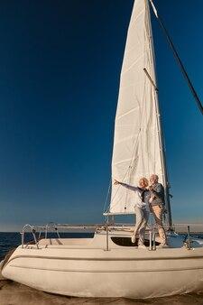 Luxe reizen over de volledige lengte van een gelukkig volwassen stel dat aan de zijkant van een zeilboot of jachtdek staat