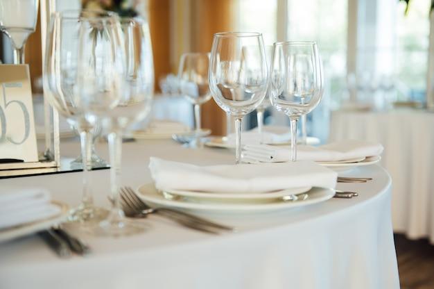 Luxe restaurant. luxe interieur, witte tafels, serveerschalen en glazen voor gasten.