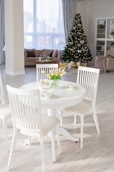 Luxe rijk duur appartement interieur in lichte kleuren. stijlvol eigentijds minimalistisch ontwerp. vol zonlicht. veel ruimte versierd met kerstboom