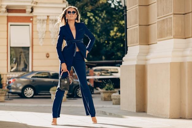 Luxe rijke vrouw gekleed in een elegante stijlvolle blauwe pak wandelen in de stad op zonnige herfstdag met portemonnee