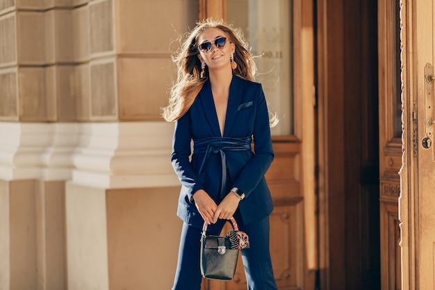 Luxe rijke vrouw gekleed in een elegante stijlvolle blauwe pak wandelen in de stad op zonnige zomerdag met portemonnee
