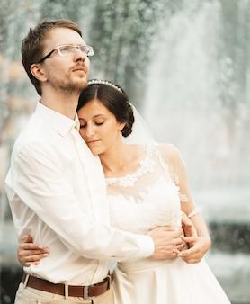 Luxe romantische gelukkige bruid en bruidegom vieren huwelijk op de achtergrond van de oude zonnige stad