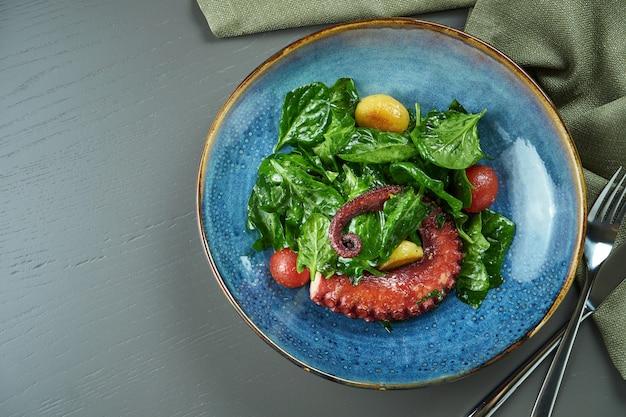 Luxe salade met gegrilde octopus, tomaten en spinazie in een blauw bord op een houten tafel. bovenaanzicht, ruimte kopiëren, plat leggen