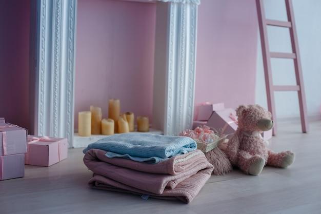 Luxe schoon helder wit interieur. een ruime kamer met zonlicht en bloemen in vazen, met een sfeerhaard, schattige roze plaids en een vaas met marshmallows. idee en concept van een meisjeskamer