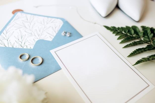 Luxe set trouwkaarten, trouwringen, elegante accessoires van de bruid op een witte achtergrond.