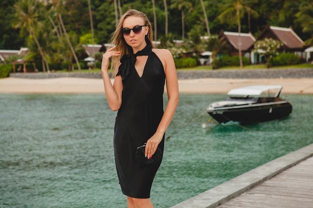 Luxe sexy aantrekkelijke vrouw gekleed in zwarte jurk poseren op pier in luxeresort, zonnebril, zomervakantie, tropisch strand
