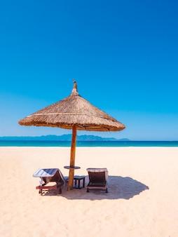 Luxe strand met parasol en stoelen in de buurt van de oceaan