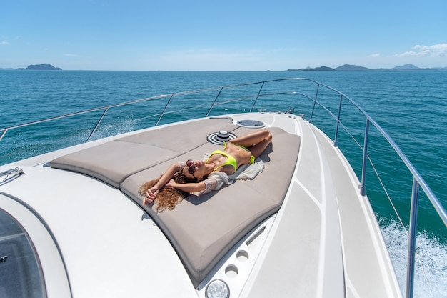 Luxe vakantie. jong mooi vrouwelijk model dat en op zee op het dek van een jacht ligt sunbuthing.