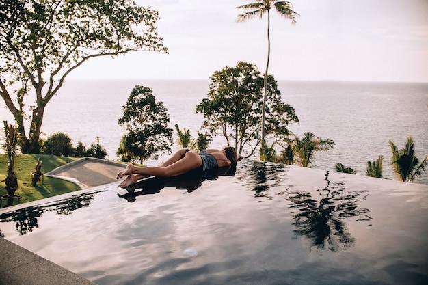Luxe vakantie reizen achteraanzicht van vrouw ontspannen in oneindig zwembad op zomer strandresort. kaukasische meisjestoerist op wellness-spa-ontspanning.