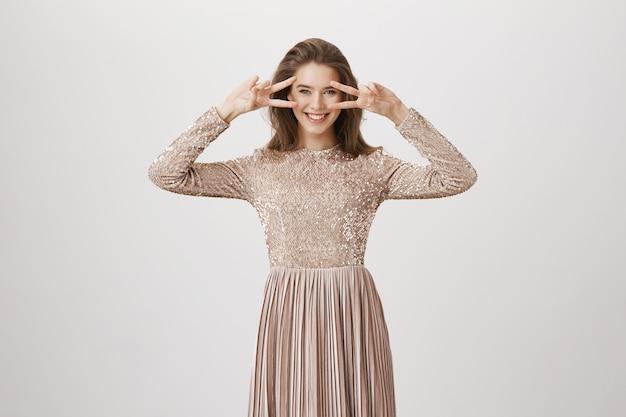 Luxe vrouw in avondjurk tonen vredesteken, glimlachend