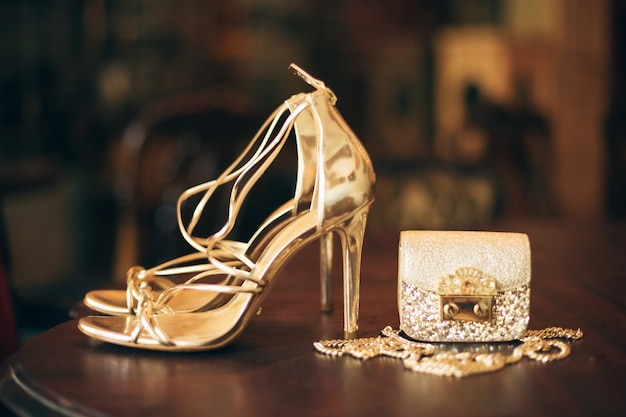 Luxe vrouw mode-accessoires, gouden hakken, kleine avondtasje, elegante stijl, vintage stijl, sandalen schoeisel