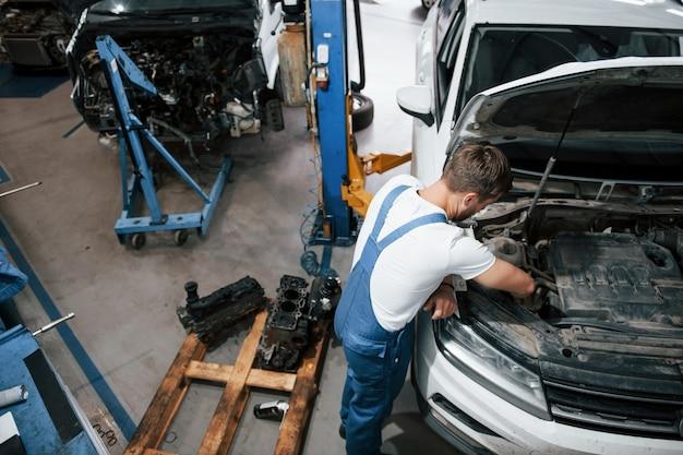 Luxe witte auto. werknemer in het blauw gekleurde uniform werkt in de autosalon