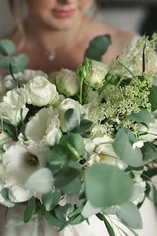 Luxe witte bruiloft boeket in de handen van de bruid