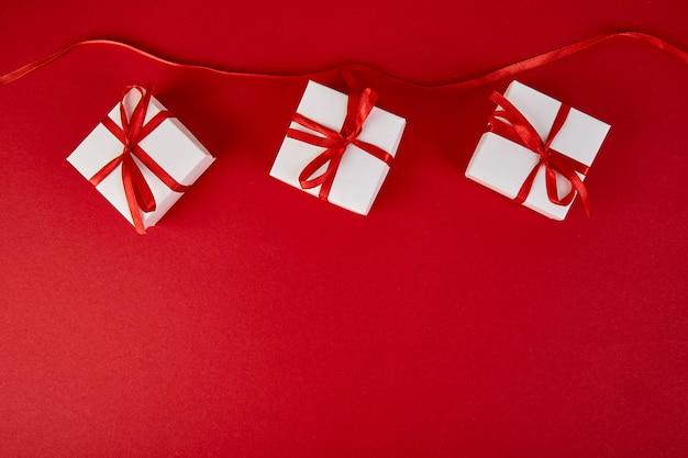 Luxe witte geschenkdozen met rood lint op rode achtergrond. valentine day, christmas, verjaardagsfeestje presenteert. moeder of vrouwendag. plat liggen. bovenaanzicht.
