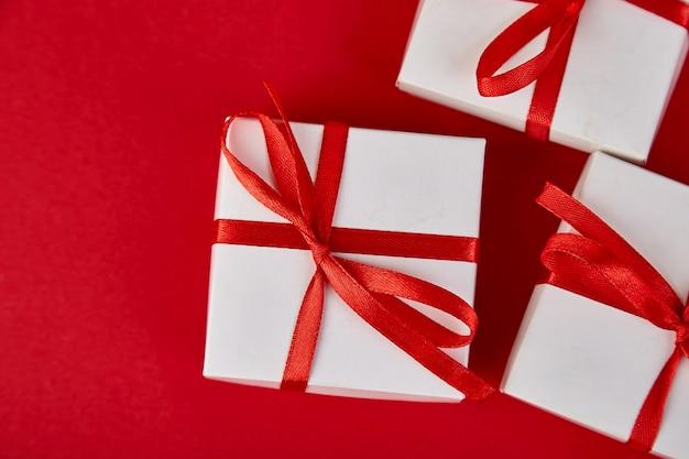 Luxe witte geschenkdozen met rood lint op rode achtergrond.