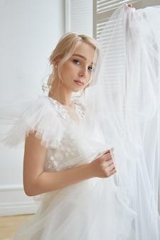 Luxe witte trouwjurk op het lichaam van het meisje. nieuwe collectie trouwjurken. ochtendbruid, een vrouw die op de bruidegom wacht voor de huwelijksceremonie. jonge bruid in een lange jurk