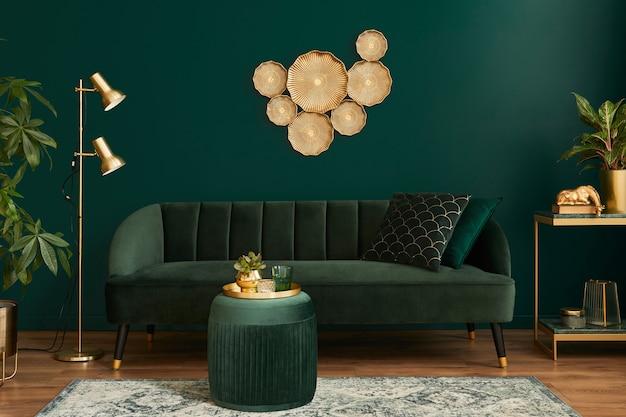 Luxe woonkamer in huis met modern interieur, groen fluwelen bank, salontafel, poef, gouden decoratie, plant, lamp, tapijt, kussens en elegante accessoires..