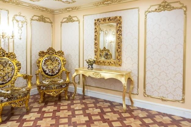 Luxe woonkamer interieur met prachtige oude bewerkte meubels van goudkleur met decoraties aan de muren in de stijl van het koninklijk paleis