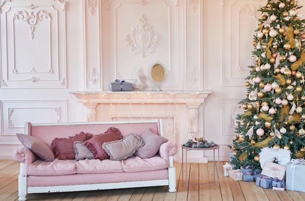 Luxe woonkamer interieur met sofa versierde chique kerstboom, geschenken en kussens. klassiek interieur in roze tinten. kerst thuis.