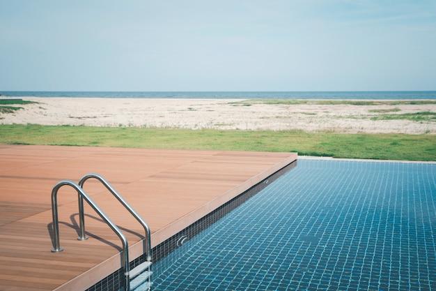 Luxe zwembad met trap en houten dek bij hotel aan het strand