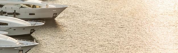 Luxejacht geparkeerd op een kanaal met de zon naar beneden in fort lauderdale. haven van fort lauderdale met zonsondergang in de jachthaven