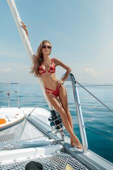 Luxevakantie: mooie blondevrouw in open waterzee op jacht die sexy rode bikini en rode zonnebril dragen. zomertijd. vakantie op een tropisch eiland.