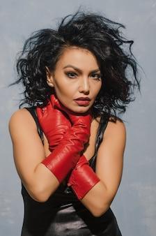 Luxueuze aziatische vrouw in zwarte leerkleding en rode handschoenen die bij de keel houden. dominante fetisj dame.