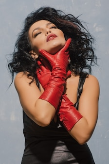 Luxueuze aziatische vrouw in zwarte leerkleding en rode handschoenen die bij de keel houden.