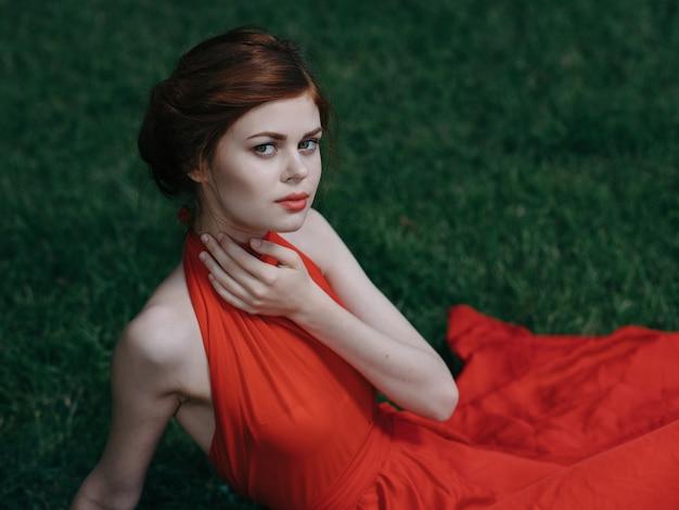 Luxueuze vrouw in rode aantrekkelijke kleding de decoratie van de groene grasvrije tijd