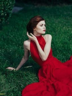Luxueuze vrouw in rode aantrekkelijke kleding de groene decoratie van de grasvrije tijd