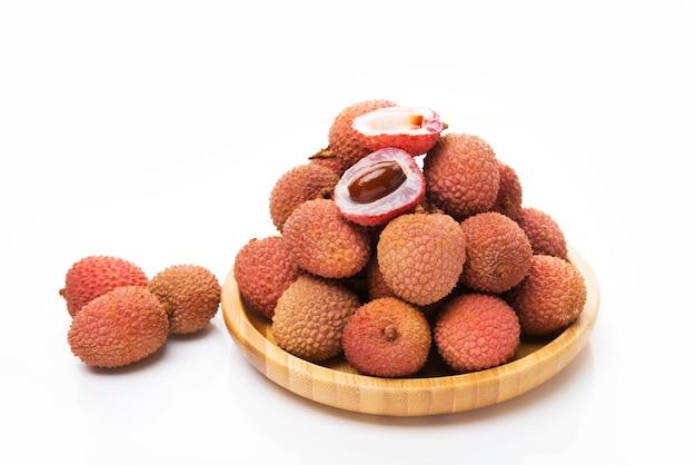 Lychee fruit op een houten plaat geïsoleerd op een witte achtergrond
