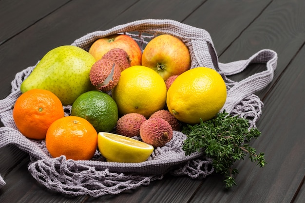 Lychee, peer, appels en citroen in herbruikbaar netzakje. donkere houten achtergrond. bovenaanzicht