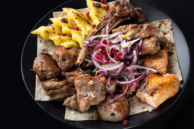 Lyulya kebab, shish kebab, gegrilde zalmvis, ui en granaatappelkorrels op zwarte plaat