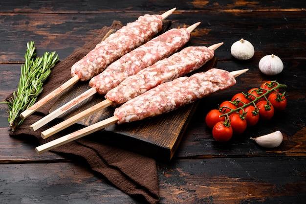 Lyulya-kebab, vleesgerecht voor kookset, met grillingrediënten, op oude donkere houten tafelachtergrond