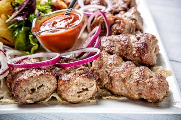 Lyulyakebab met rode saus en ui op witte plaat dichte omhooggaand