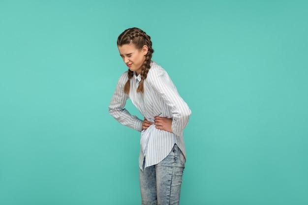 Maagpijn, profiel zijaanzicht portret van ongelukkig, verdrietig jong meisje in blauw gestreept t-shirt en staarthaar dat staat en pijn op haar buik voelt. indoor studio opname geïsoleerd op groene achtergrond.