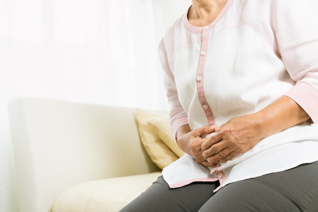 Maagpijn van oude vrouw thuis, gezondheidszorgprobleem van hoger concept