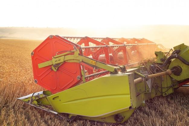 Maaidorser dicht omhoog. maaidorser het oogsten tarwe bij zonsondergang.