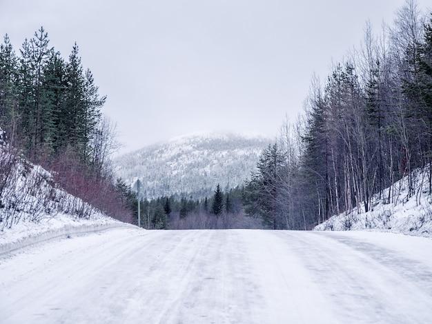 Maak de gladde winterweg leeg, een steile klim de heuvel op.