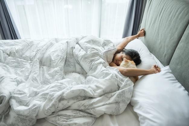 Maak de vrouw en kat wakker in bed in de ochtend