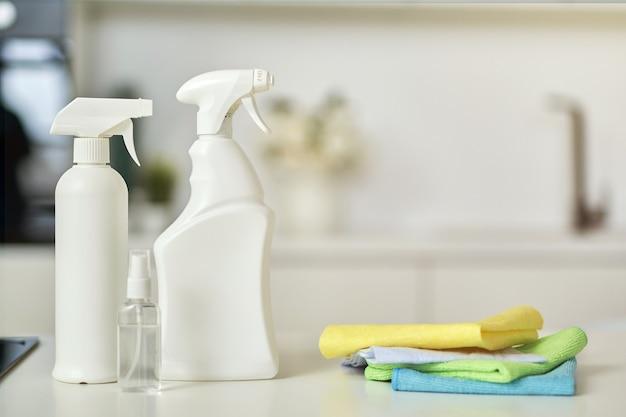 Maak een close-up shot van wasmiddelflessen en stapel tapijten op het keukenoppervlak schoon