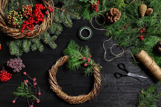 Maak een kerstkrans met je eigen handen sparrentak kerstkrans en geschenken op een zwart hout...