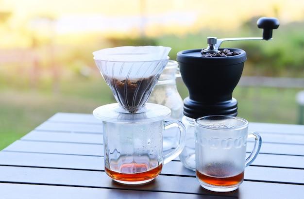 Maak een kopje handdruppelkoffie in een glazen pot op buitenshuis, druppel koffiebarista die water giet